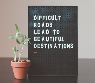 A sign with the words difficult roads lead to beautiful destinations